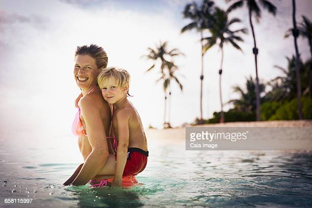 Portrait smiling mother piggybacking son in tropical ocean