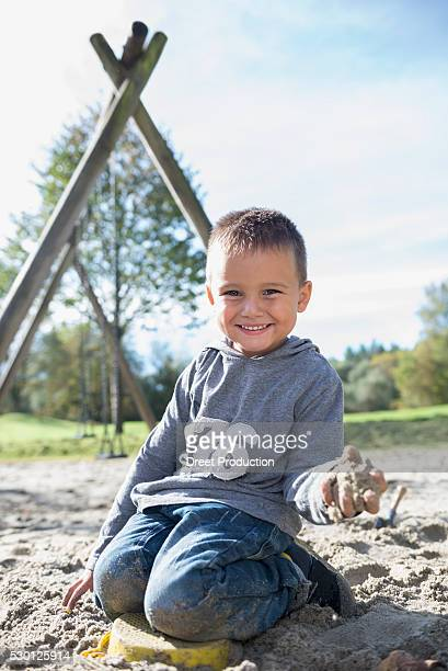 Portrait smiling small boy sandbox playground