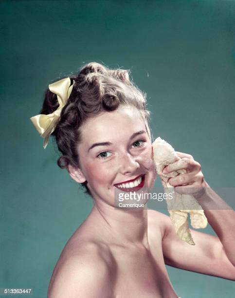 Portrait smiling teen girl washing face with washcloth Los Angeles California 1949
