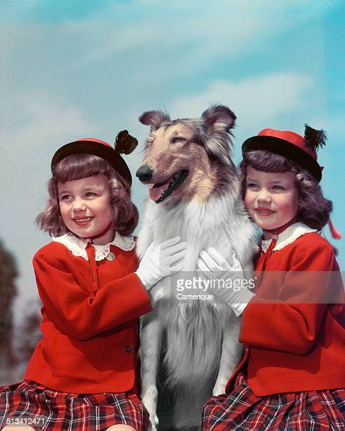 Portrait smiling twin girls wearing matching red sweaters plaid skirts hats and gloves posing with collie dog Los Angeles California 1949