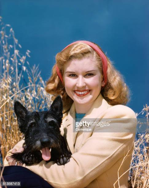 Portrait smiling woman holding black scottie dog , Los Angeles, California, 1949.