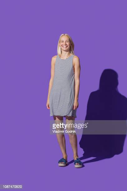 portrait smiling woman in striped dress against purple background - purple dress stock pictures, royalty-free photos & images