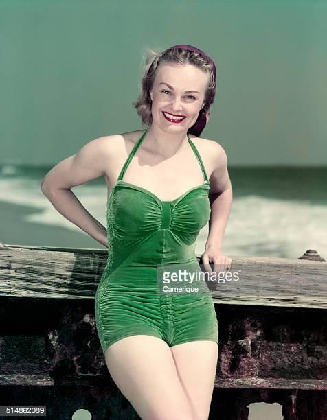 Portrait smiling woman wearing green velvet bathing suit posing leaning on pier Los Angeles California 1949