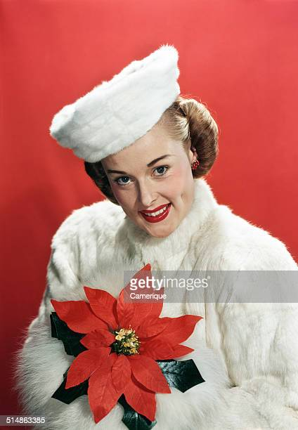 Portrait smiling woman wearing white fur overcoat and hat holding poinsettia Los Angeles California 1949