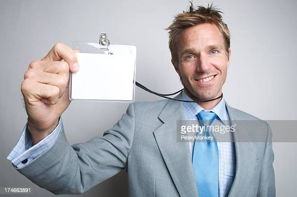 Portrait smiling young businessman holding up ID
