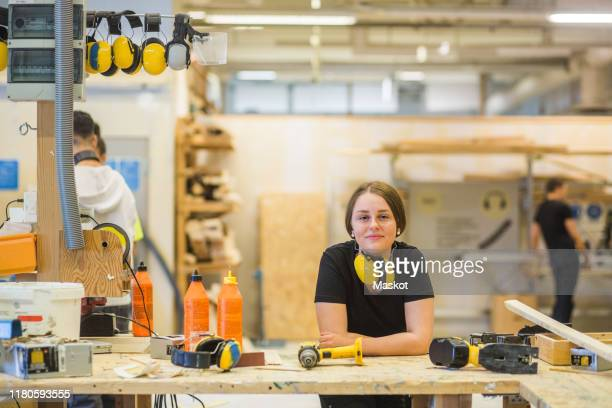 portrait smiling young female carpentry trainee leaning on workbench with power tools at illuminated workshop - trainee stock pictures, royalty-free photos & images