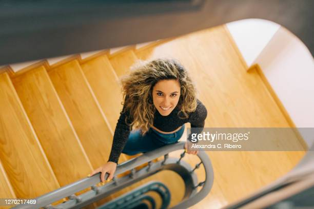 portrait smiling young woman on wooden staircase - moving up stock pictures, royalty-free photos & images