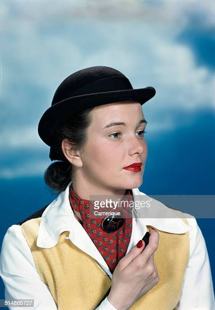 Portrait teen girl wearing equestrian outfit derby hat holding riding crop Los Angeles California 1949