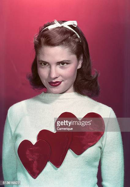 Portrait teen girl wearing sweater with three red valentine hearts, Los Angeles, California, 1949.