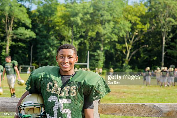 portrait teenage male american football player holding helmet at playing field - high school football stock pictures, royalty-free photos & images
