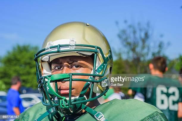 Portrait teenage male American football player wearing helmet at playing field