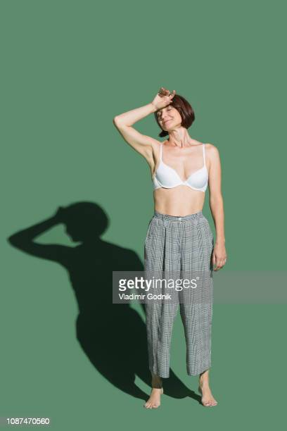 portrait tired woman in bra against green background - bras stock pictures, royalty-free photos & images
