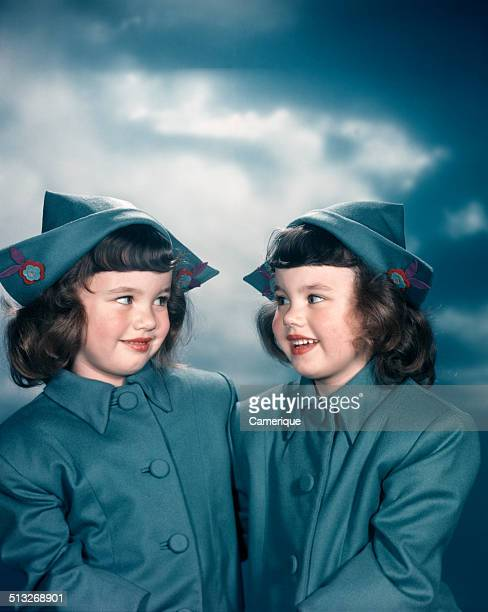 Portrait twin girls wearing blue dutch outfits overcoats traditional pointed hats Los Angeles California 1949