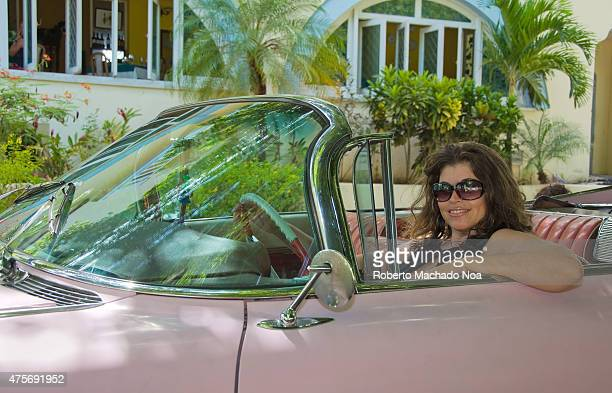 Portrait woman in old American car she wears glasses sitting behind the wheel of a retro car Palm trees grow near the house in the background