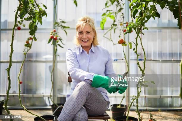portrait woman sitting in greenhouse - environmental issues imagens e fotografias de stock