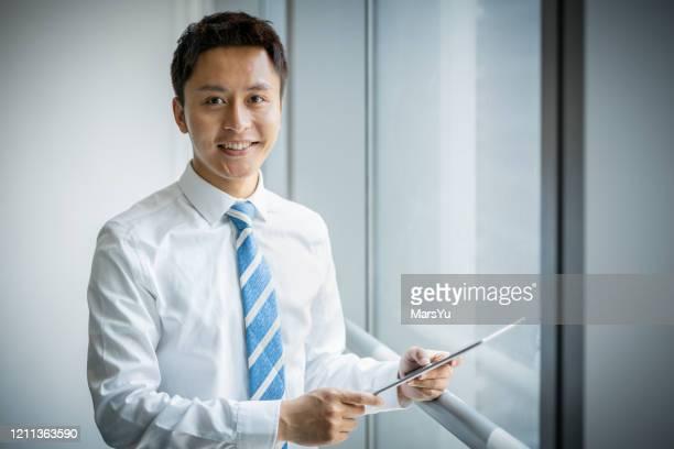 retrato jovem empresário asiático segurando tablet/smartphone em terno formal no escritório - extremo oriente - fotografias e filmes do acervo