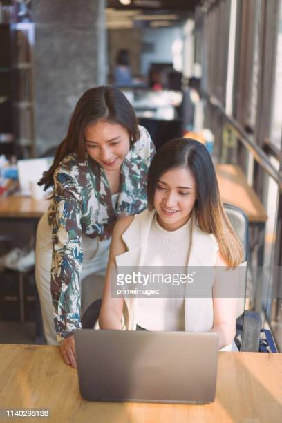 portrait young asian creative business person working success project with team business people weare casual suit outfit working happy action in modern coworking space - vertical imagens e fotografias de stock