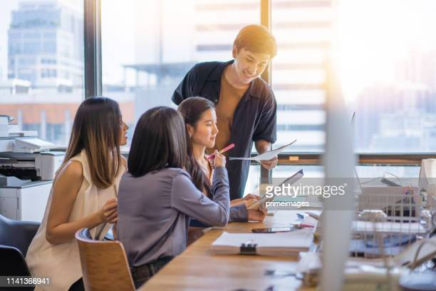 portrait young asian creative business person working success project with team business people weare casual suit outfit working happy action in modern coworking space - financial technology stock pictures, royalty-free photos & images