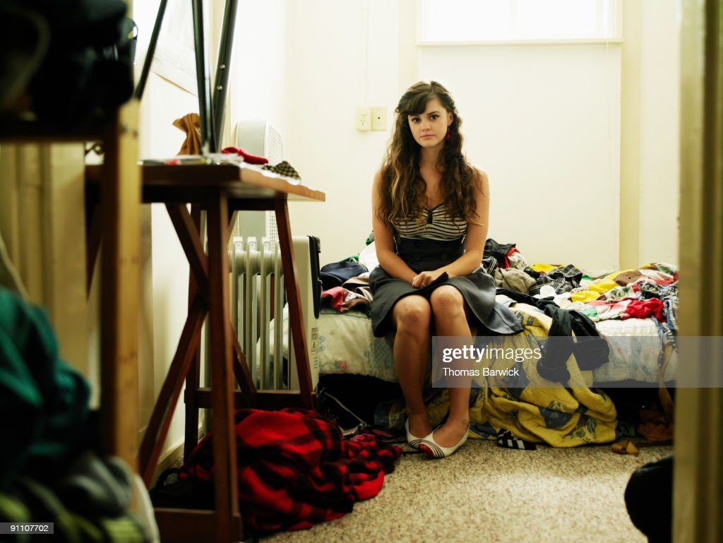 Portrait young woman sitting on bed in bedroom : Stock Photo