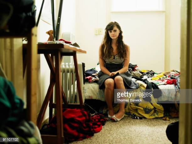 Portrait young woman sitting on bed in bedroom