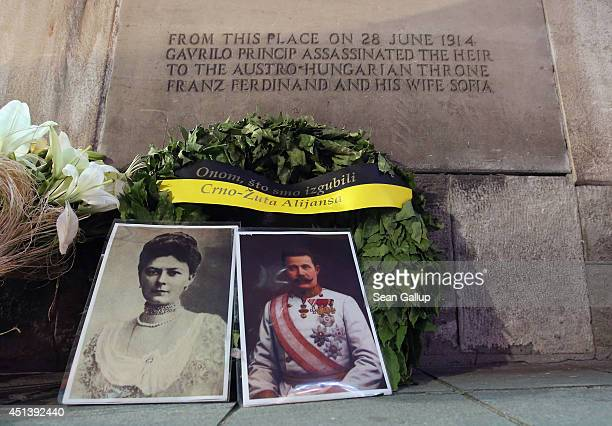 Portraits of Austrian Archduke Franz Ferdinand and his wife, Duchess Sophie, stand with a wreath under a plaque marking the spot where they were...