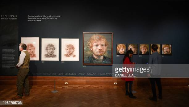 TOPSHOT Portraits of British musician Ed Sheeran painted by Irish artist Colin Davidson are pictured on display during a press preview of the...
