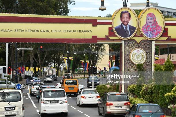 Portraits of Brunei's Sultan Hassanal Bolkiah and Queen Saleha are seen beside a slogan in Bahasa Melayu that reads 'obedience to Allah loyalty to...