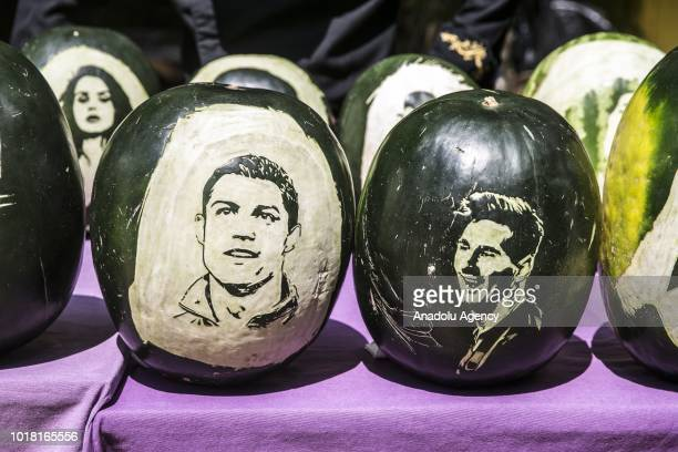 Portraits of Cristiano Ronaldo and Lionel Messi carved on watermelons by cook Halil Bozkurt are seen in Turkey's Hatay on August 17 2018 Bozkurt...
