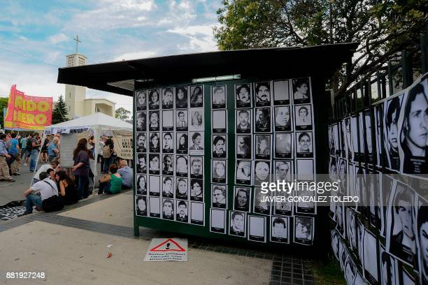 Portraits of disappeared during the last Argentine military dictatorship are displayed outside Comodoro Py federal courts during the sentencing...