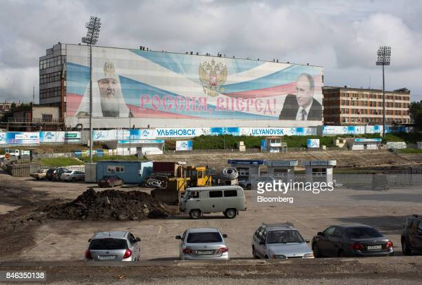 Portraits of Kirill of Moscow partriach of the Russian Orthodox Church left and Vladimir Putin Russia's president stand on the side of a building...