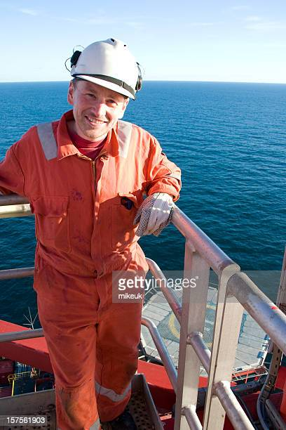 Portraits of man in orange jumpsuit on an oil rig