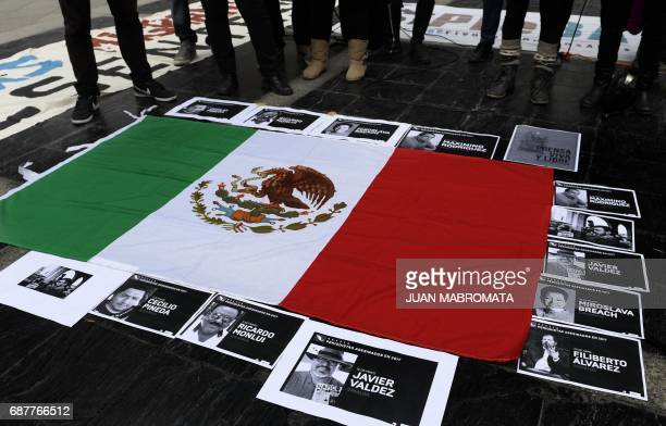 Portraits of Mexican journalist Javier Valdez murdered in Culiacan Sinaloa Mexico on May 15 were placed on a Mexican flag during a protest in front...