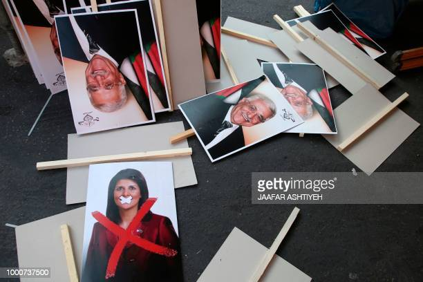 Portraits of Palestinian president Mahmud Abbas and US Ambassador to the United Nations Nikki Haley lie on the ground during a rally in support to...