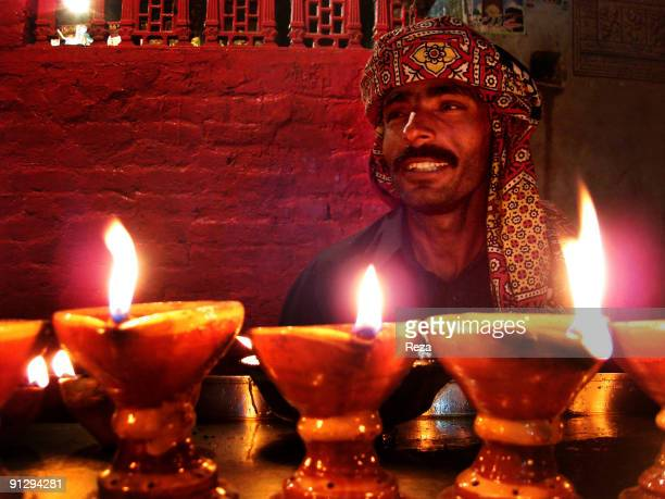 Portraits of pilgrims praying by candles inside the shrine of Lal shahbaz Qalandar a 13th century Sufi Master worshiped alike by Hindus and Muslims...