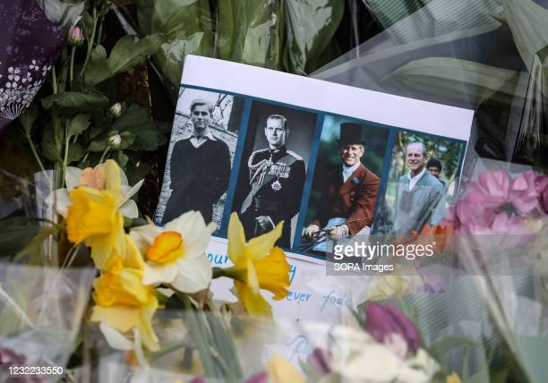 Portraits of Prince Philip seen next to flowers during the tribute. Members of the public leave floral tributes for the late Prince Philip outside...