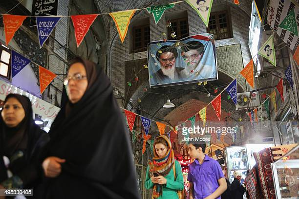 Portraits of the late Ayatollah Khomeini and Iran's current supreme leader Ayatollah Khamenei hang over shoppers in the historic Bazare Bozorg on...