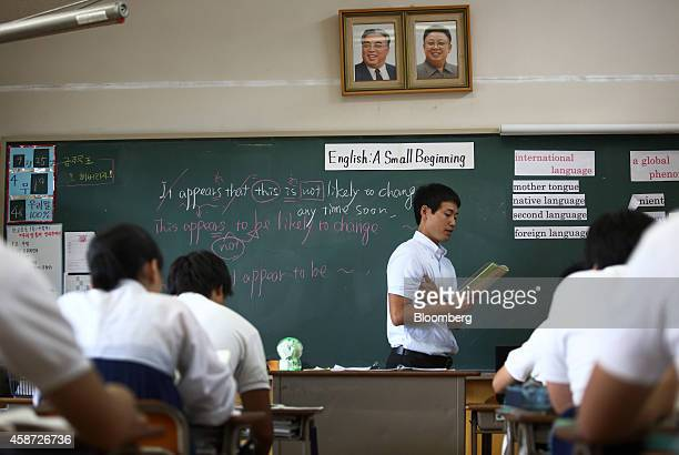 Portraits of the late North Korean leaders Kim Il Sung left and Kim Jong Il are displayed in a classroom as a teacher conducts an English class at...