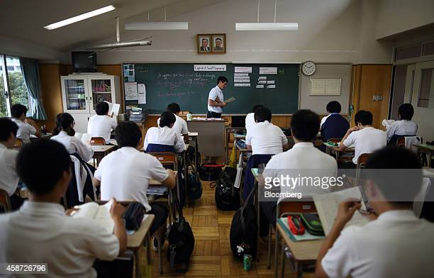 Portraits of the late North Korean leaders Kim Il Sung left and Kim Jong Il are displayed in a classroom as a teacher conducts a class with students...