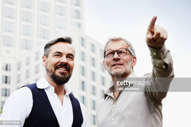 portraits of two businessmen standing in front of a modern apartment building