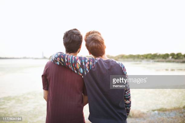 portraits of two male friends back view enjoying the scenery - arm around stock pictures, royalty-free photos & images