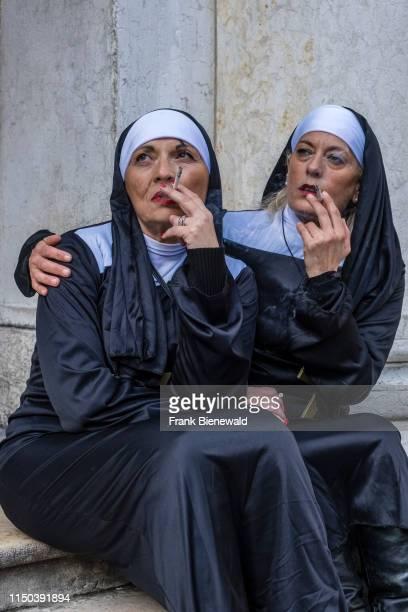 Portraits of two women in beautiful creative nun costumes, smoking, posing at San Marco Square, Piazza San Marco, celebrating the Venetian Carnival.