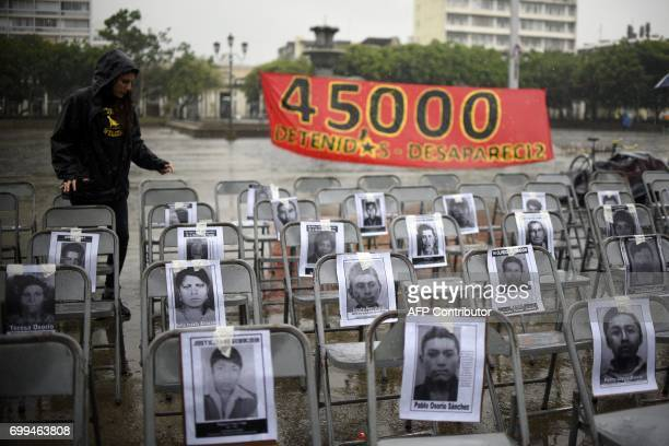 Portraits of victims of forced disappearance hang on empty chairs during the ceremony to commemorate the National Day of the Victims of Enforced...