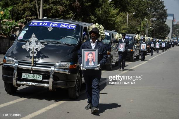 Portraits of victims of the crashed accident of Ethiopian Airlines are hold beside funeral cars during the mass funeral at Holy Trinity Cathedral in...