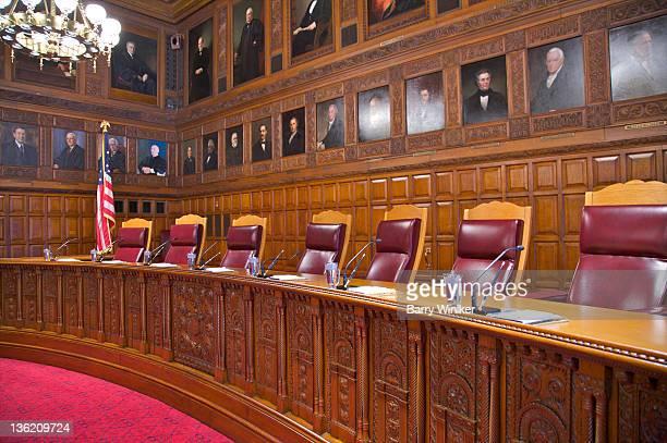 Portraiture above carved wood desk in courtroom.