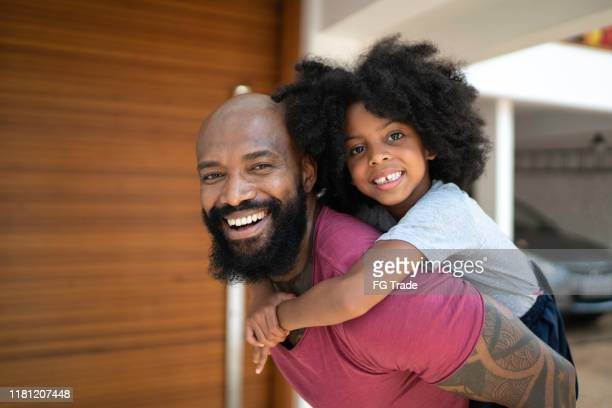 portrat of father giving his daughter a piggyback ride - fathers day stock pictures, royalty-free photos & images
