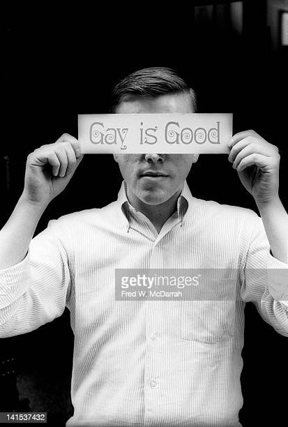Portriat of American gay rights activist Craig Rodwell as he holds a bumper stickersized sign that reads 'Gay is Good' over his eyes New York New...