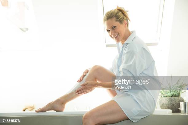 portriat of smiling woman sitting on edge of bathtub creaming her leg - older woman legs stock photos and pictures