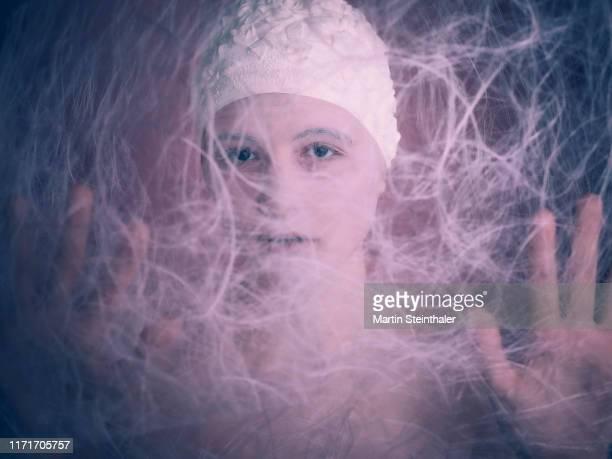 porträt mädchen mit badehaube hinter netz - geheimnisvoll und schützend - porträt stock pictures, royalty-free photos & images