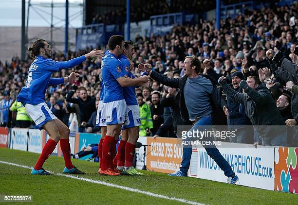 Portsmouth fan jumps on to the pitch as Portsmouth's English midfielder Gary Roberts celebrates scoring his team's first goal during the English FA...