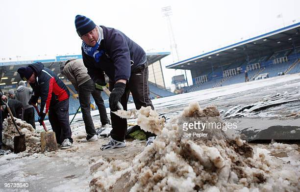 Portsmouth fans clear snow from Fratton Park stadium before the weekend match against Birmingham City on December 13 2009 in Portsmouth England All...